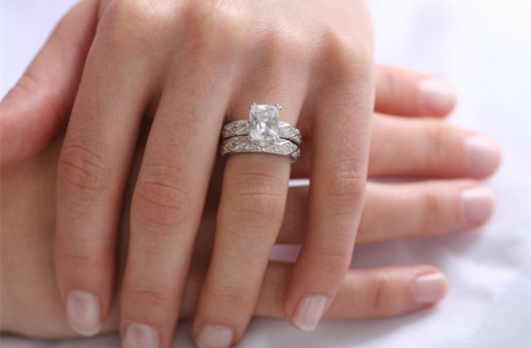Engagement and wedding ring sets on finger